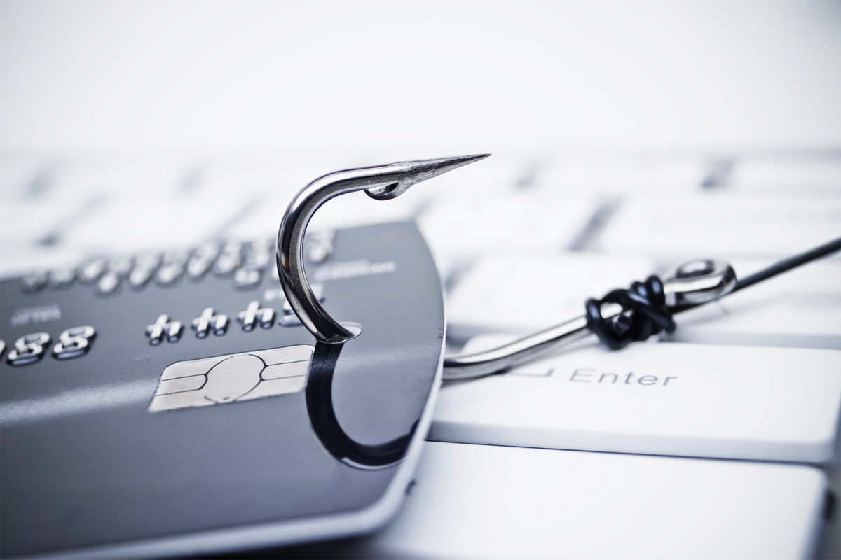 credit card phishing - piles of credit cards with a fish hook on computer keyboard-1.png © Adobe Stock