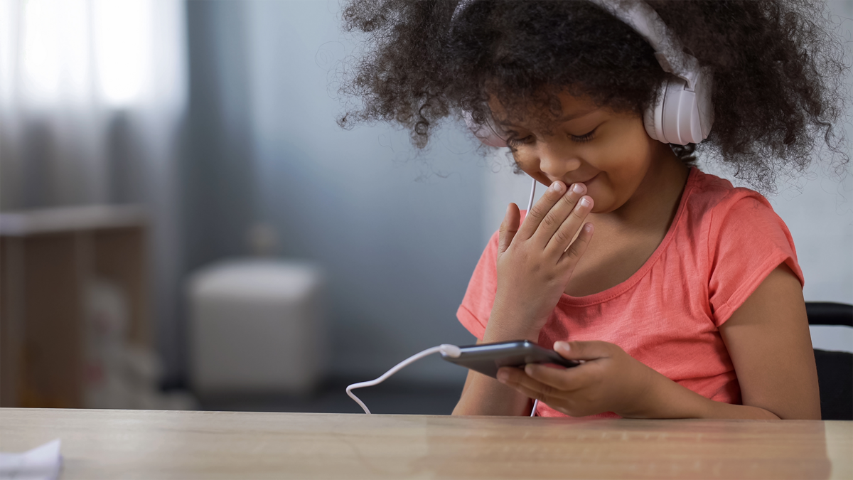 Little black girl smiling while surfing internet on smartphone, parental control-1.png © Adobe Stock